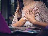 istock Closeup woman having heart attack. Woman touching breast and having chest pain after long hours work on computer. Office syndrome concept. 847527892