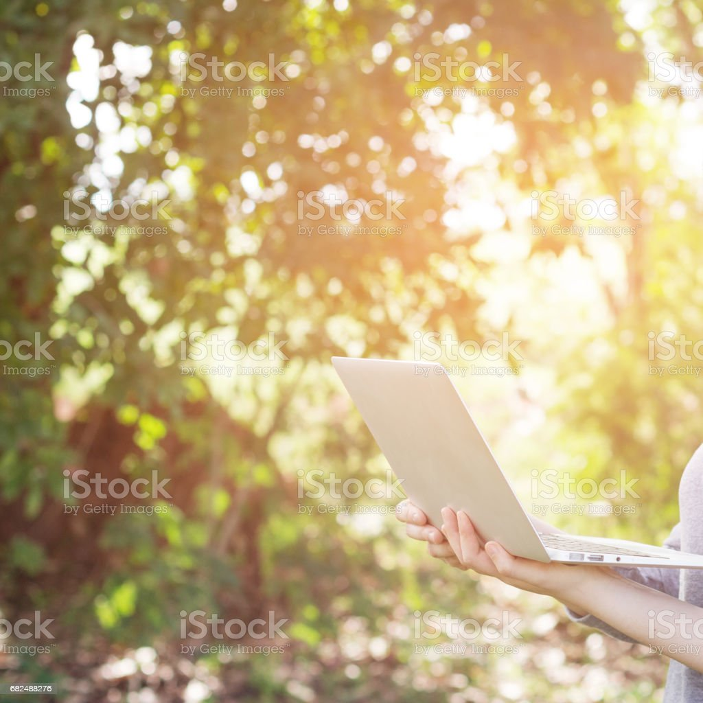 Close-up woman holding computer at park., relax time. royalty-free stock photo