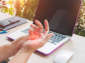 istock Closeup woman holding her painful hand from using computer. Office syndrome hand pain by occupational disease. 840753686
