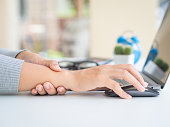 istock Closeup woman holding her wrist pain from using computer long time. Office syndrome concept. 1018203952