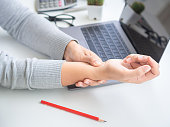 istock Closeup woman holding her wrist pain from using computer long time. Office syndrome concept. 1018203974