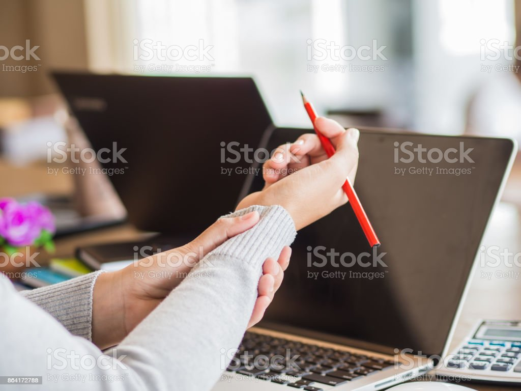 Closeup woman holding her wrist pain from using computer long time. Office syndrome concept. royalty-free stock photo
