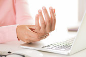 istock Closeup woman holding her wrist pain from using computer. Office syndrome hand pain by occupational disease. 1014847830