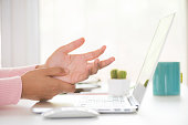 istock Closeup woman holding her wrist pain from using computer. Office syndrome hand pain by occupational disease. 1032359314