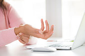 istock Closeup woman holding her wrist pain from using computer. Office syndrome hand pain by occupational disease. 1042128088