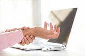 istock Closeup woman holding her wrist pain from using computer. Office syndrome hand pain by occupational disease. 1043713684