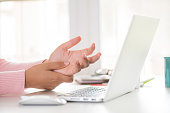 istock Closeup woman holding her wrist pain from using computer. Office syndrome hand pain by occupational disease. 1048539172