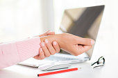 istock Closeup woman holding her wrist pain from using computer. Office syndrome hand pain by occupational disease. 1051817046