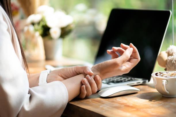 крупным планом женщина, держащая ее боль в запястье от использования компьютера. офисный синдром боли в руке от профессиональных заболеван - white background стоковые фото и изображения