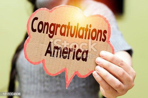 istock closeup woman holding speech bubble card with Congratulations America 1215004506