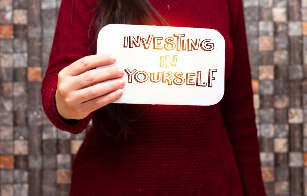 Nahaufnahme Frau hält weißen Karton Karte mit Investition in sich selbst – Foto