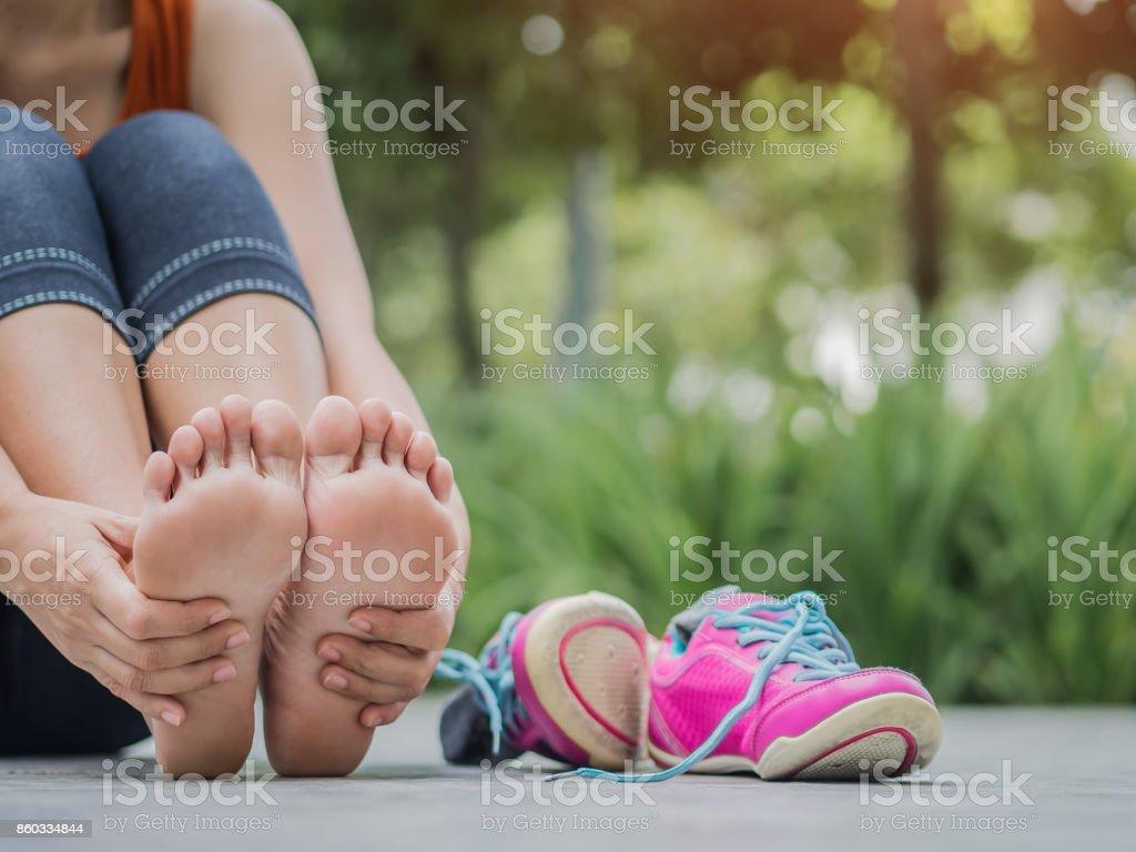 Detalle mujer masajeando sus pies dolorosos durante el ejercicio.   Ejecutar el concepto de lesión deportiva. - foto de stock