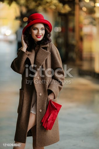 518885222istockphoto Close-up woman of 28-30 years with dark hair in a elegant coat and red accessories 1210264642