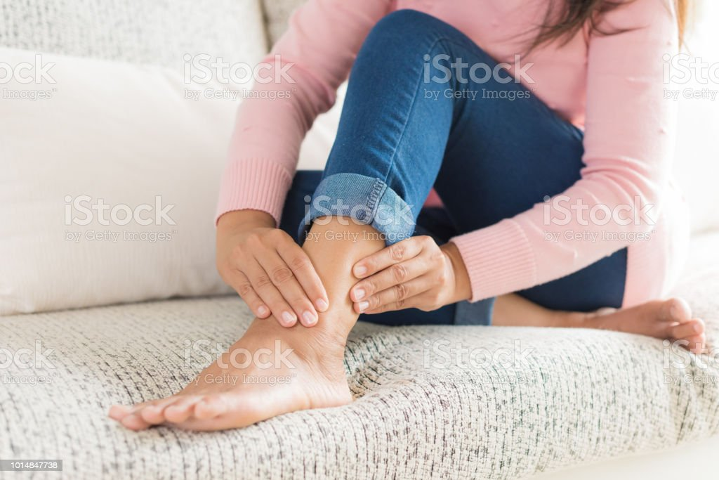 Closeup woman sitting on sofa holds her ankle injury, feeling pain. Health care and medical concept. stock photo