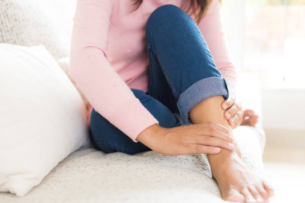 closeup woman sitting on sofa holds her foot injury, feeling pain. health care and medical concept. - slogatura foto e immagini stock