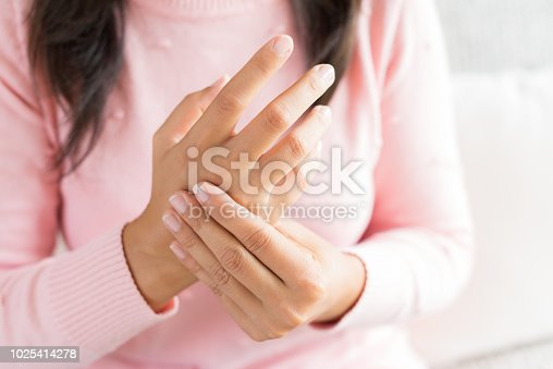 istock Closeup woman sitting on sofa holds her wrist hand injury, feeling pain. Health care and medical concept. 1025414278
