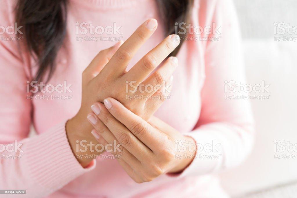 Closeup Frau sitzt auf dem Sofa hält ihr Handgelenk Handverletzung, Schmerz zu fühlen. Medizinischen Konzept. – Foto