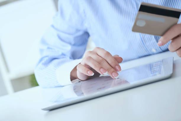 Nahaufnahme Frau Hände halten eine Kreditkarte und mit Tablet-PC für Online-Shopping. Mittlerer Teil der jungen Geschäftsfrau, die Online-Zahlungen mit Kreditkarte und Tablet. – Foto