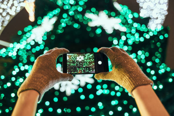 Close-up woman's hands in warm gloves Close-up woman's hands in warm gloves taking picture of illuminated green Christmas tree using mobile phone in city at night. digital viewfinder stock pictures, royalty-free photos & images