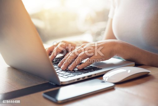 Closeup woman's hands typing on a laptop that is on a wooden desk with a mobile smartphone and mouse computer