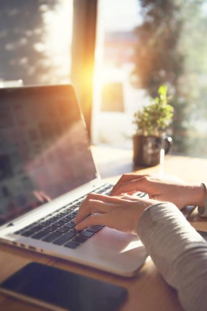 在一台筆記本電腦上打字的特寫女人的手 - 垂直構圖 個照片及圖片檔
