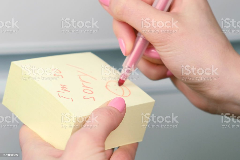 Closeup woman's hands write on yellow sticker paper sheets words i'm so sorry and laugthing emoticon. stock photo