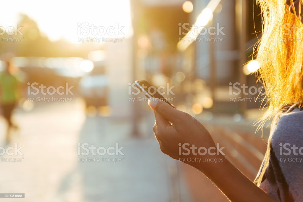 closeup women using smartphone at sunset royalty-free stock photo