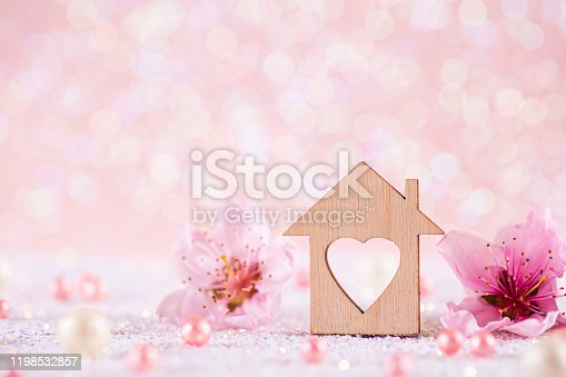 Closeup wooden house with hole in form of heart surrounded by spring flowering tree branches on glitter sparkling pink background with bokeh. Natural composition for Valentine or Mother day with copy space. Concept of sweet home