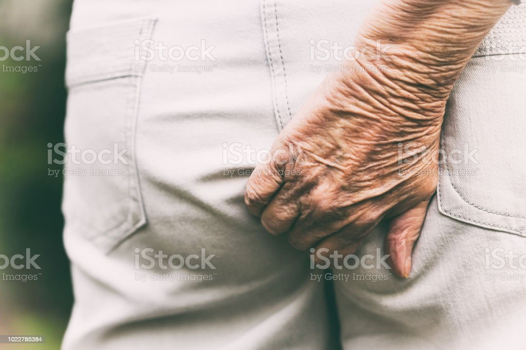 Close-up wrinkled old hand scratching bottom through trousers stock photo