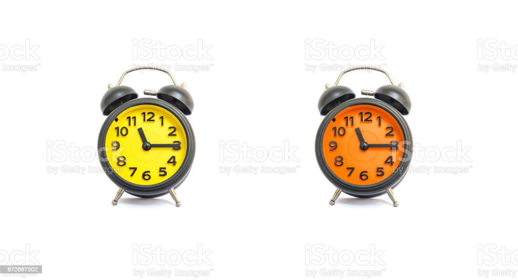 Closeup yellow alarm clock and orange alarm clock for decorate show a quarter past eleven o'clock or 11:15 a.m. isolated on white background stock photo