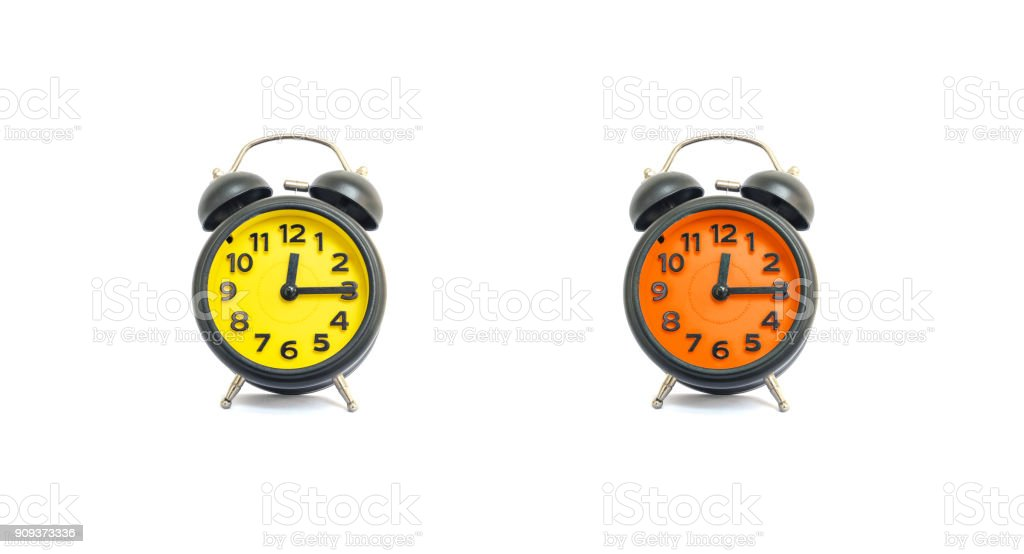 Closeup yellow alarm clock and orange alarm clock for decorate show a quarter past twelve o'clock or 12:15 a.m. isolated on white background stock photo