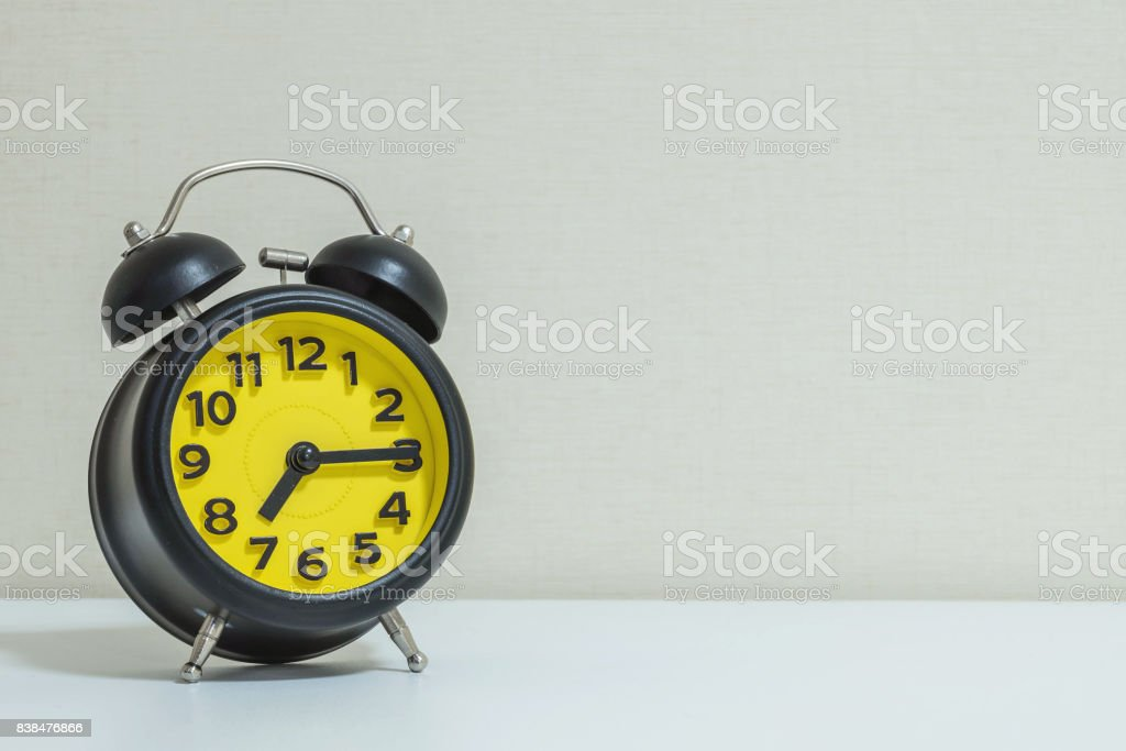 Closeup yellow and black alarm clock for decorate show a quarter past seven o'clock or 7:15 a.m.on white wood desk and cream wallpaper textured background tone with copy space stock photo