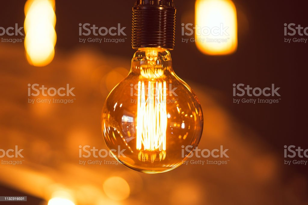 Close-up yellow light bulb on dark background. Beautiful electricity...