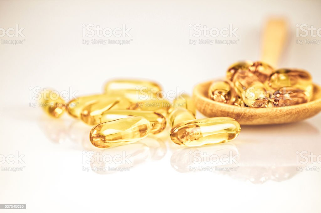 Closeup yellow soft gelatin supplement fish oil capsule stock photo