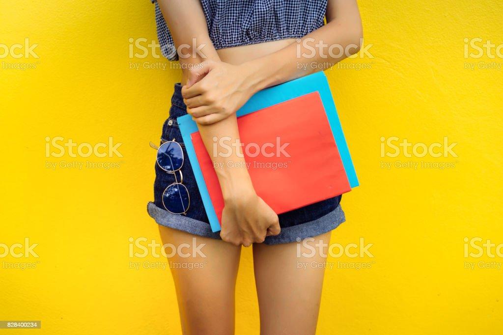 근접 촬영 영 소녀 체 노란색 배경 스튜디오에 선글라스와 함께 서 폴더 색상을 들고 스톡 사진