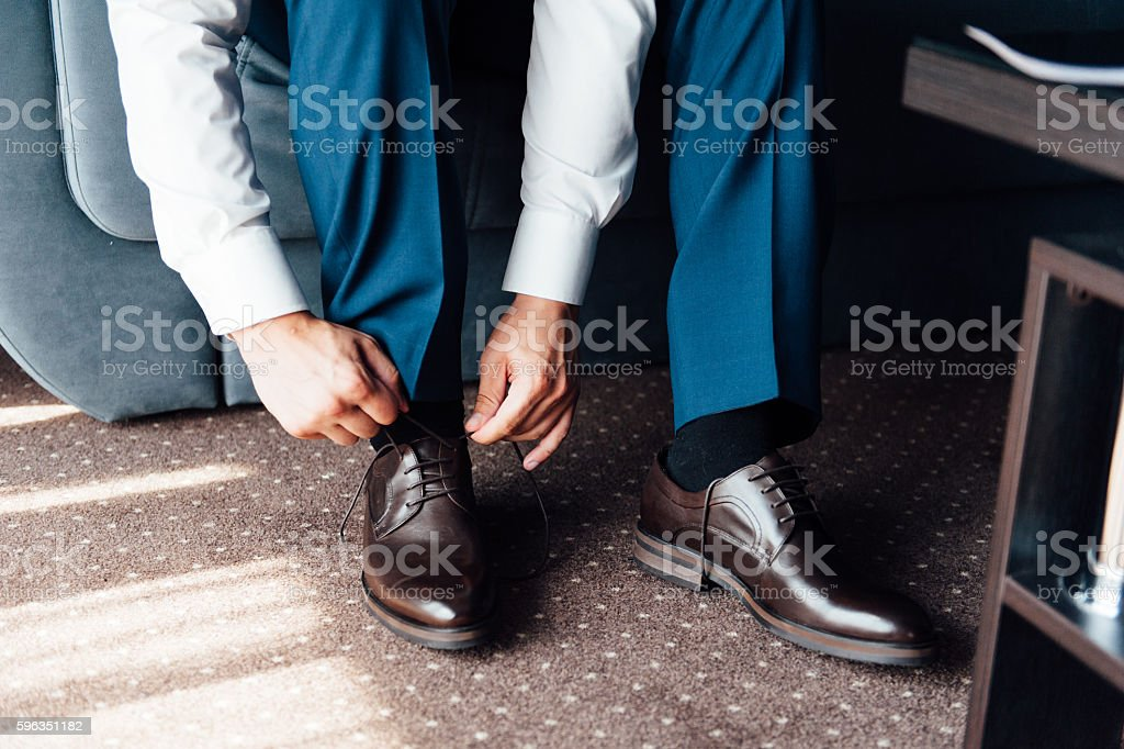 Close-up young man tying elegant shoes indoors Lizenzfreies stock-foto