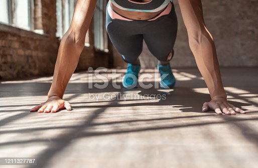 Closeup young sporty fit girl do practice individual hatha yoga instructor training Vasisthasana plank pressup arm leg support balancing pose modern spacious gym wooden floor healthy lifestyle concept