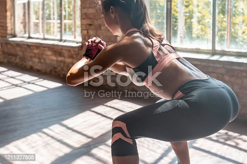 Closeup young sporty woman fitness trainer do bodyweight squats practice squatting exercise with hands clasped bending forward keep fit in modern gym wooden floor healthy lifestyle concept copy space