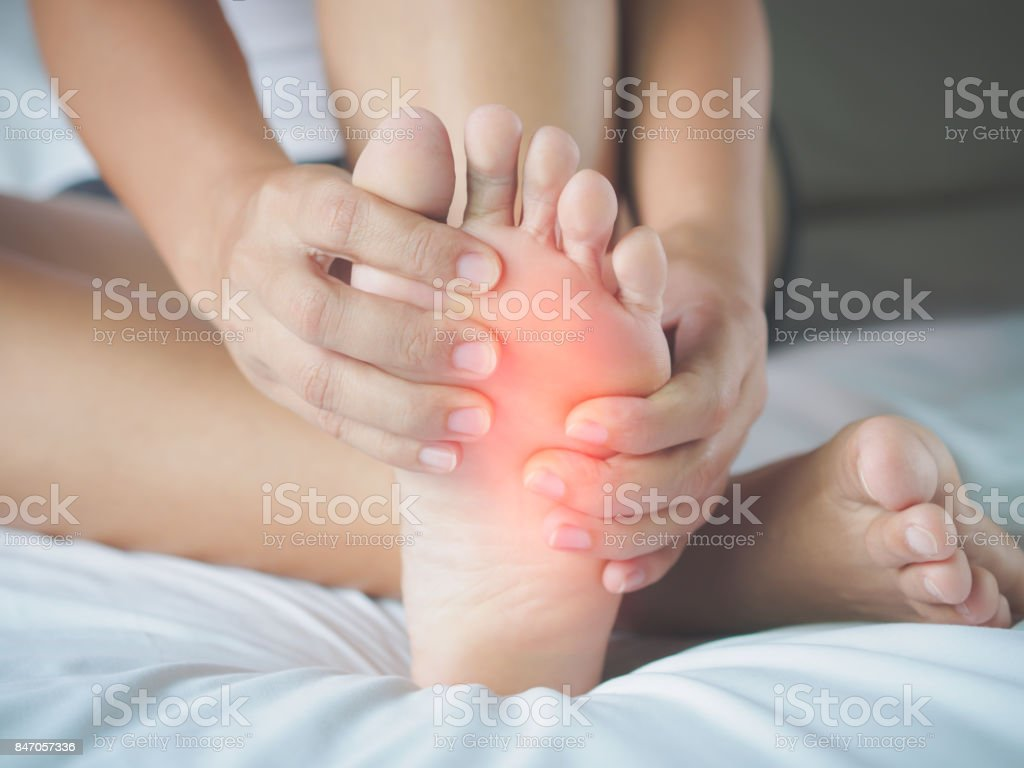 Closeup young woman feeling pain in her foot at home. Healthcare and medical concept. stock photo