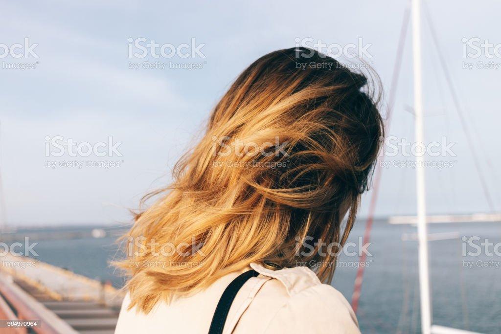 Close-up young woman looking at sea standing on embankment stock photo