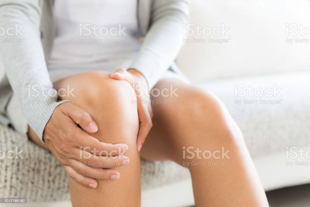 Closeup young woman sitting on sofa and feeling knee pain and she massage her knee at home. Healthcare and medical concept. - Foto stock royalty-free di Accudire