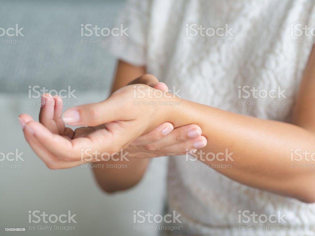 Closeup junge Frau sitzt auf dem Sofa hält ihr Handgelenk. Hand Verletzung, Schmerz zu fühlen. Medizinischen Konzept. - Lizenzfrei Anatomie Stock-Foto