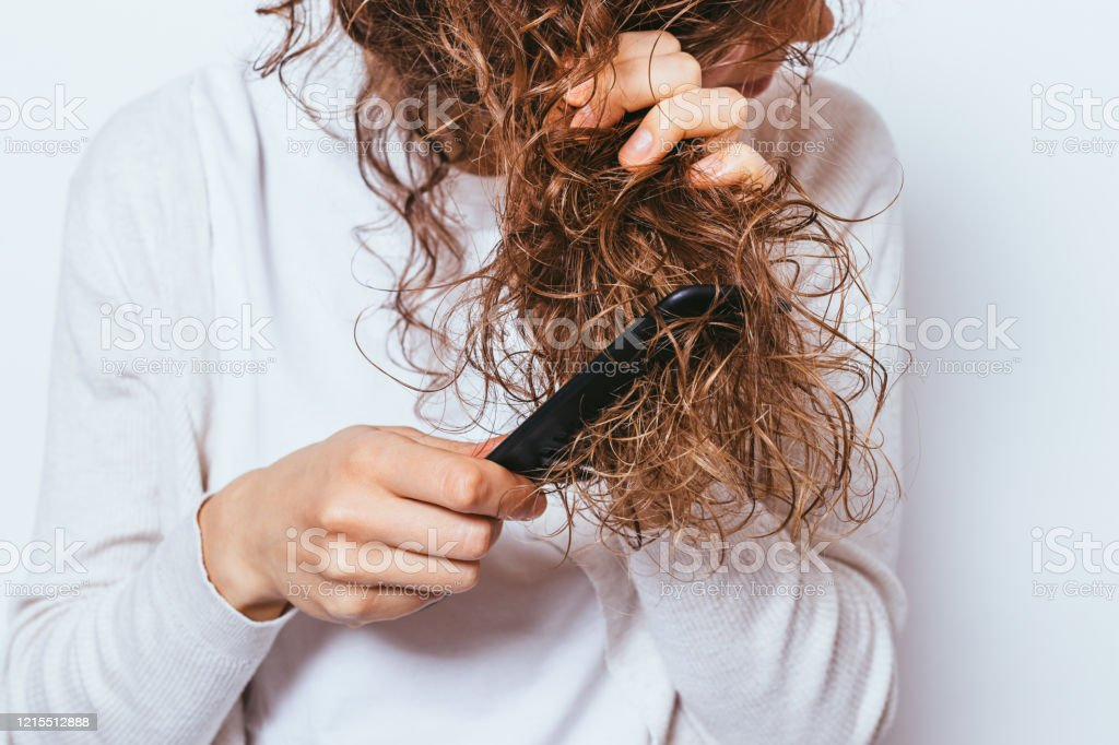 Close-up young woman wearing white shirt Close-up young woman wearing white shirt combing her tangled curly hair. Adult Stock Photo
