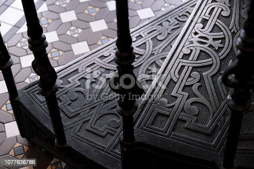 Close-ups of steps forged metal stairs with patterns. Floor with monochrome tiles.