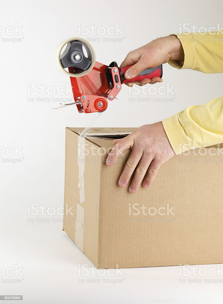 Closing a cardboard box with tape stock photo