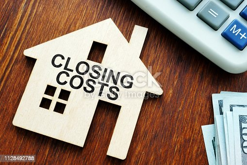 Closing costs. Model of house and money.