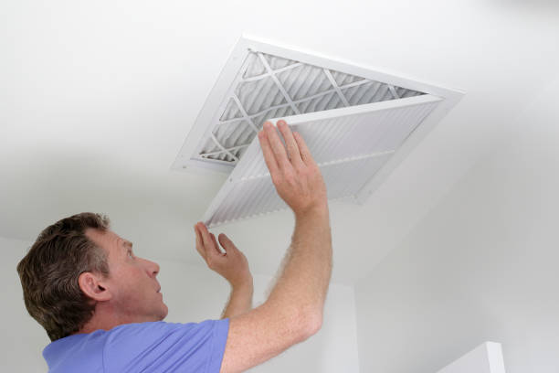 Closing Grill After Replacing Air Filter Man shutting grill of HVAC, heating ventilating and cooling after replacing the air filter. Closing ceiling grill after replacing an air filter in the ceiling. air filter stock pictures, royalty-free photos & images