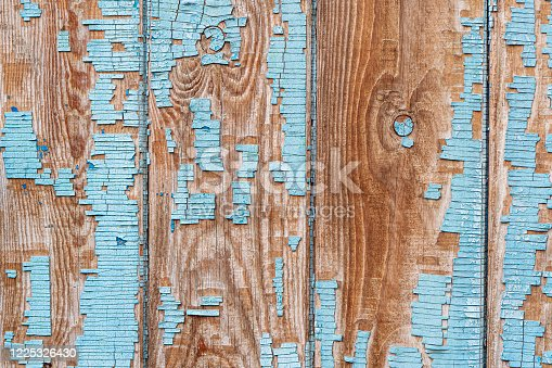 Closing on blue wooden panels of the fence close up. peeling old paint on a wooden fence.