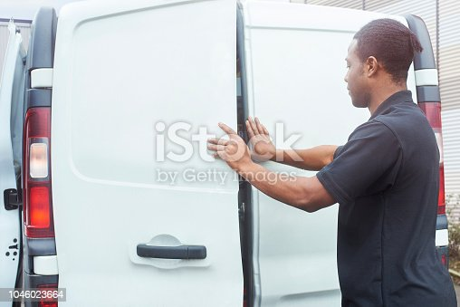 A tradesman closes the doors on the back of his van
