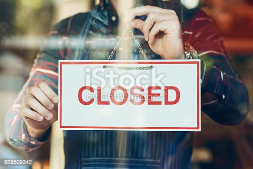 Closeup shot of a young man hanging up a closed sign in a shop window